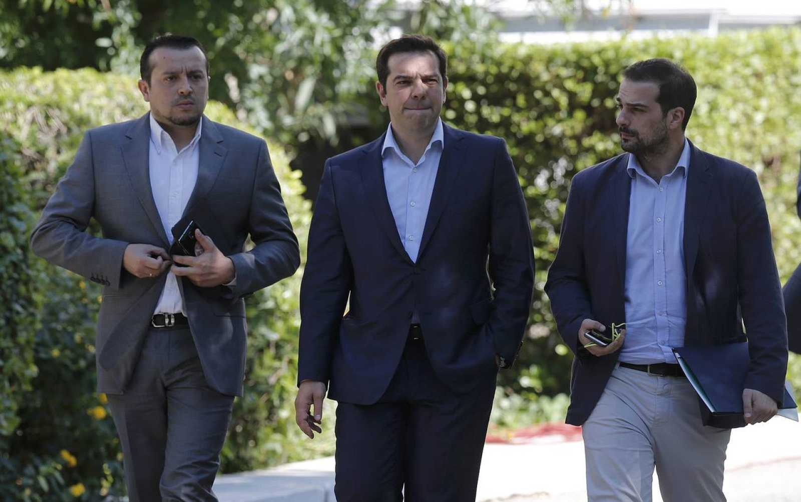 Greek Prime Minister Tsipras, Minister of State Papas and Government spokesman Sakelaridis leave the Presidential Palace for Maximos Mansion after a meeting with party leaders in central Athens