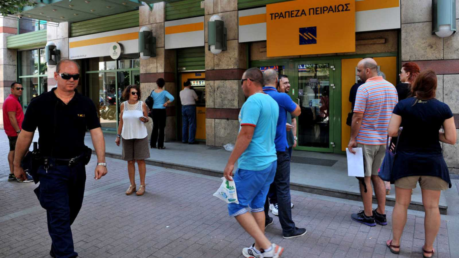 Un grupo de clientes hacen cola ante un cajero automático en Atenas