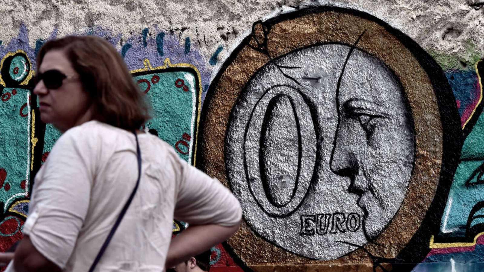 Una mujer, delante de un graffiti que muestra una moneda de cero euror en una calle del centro de Atenas