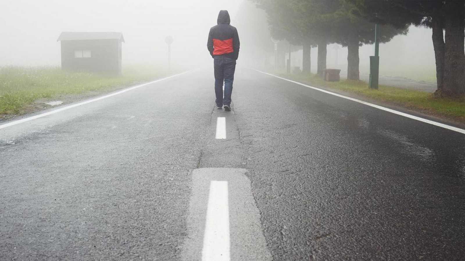 Un hombre camina solitario y de espaldas por una carretera hacia el horizonte, enmedio de la niebla.