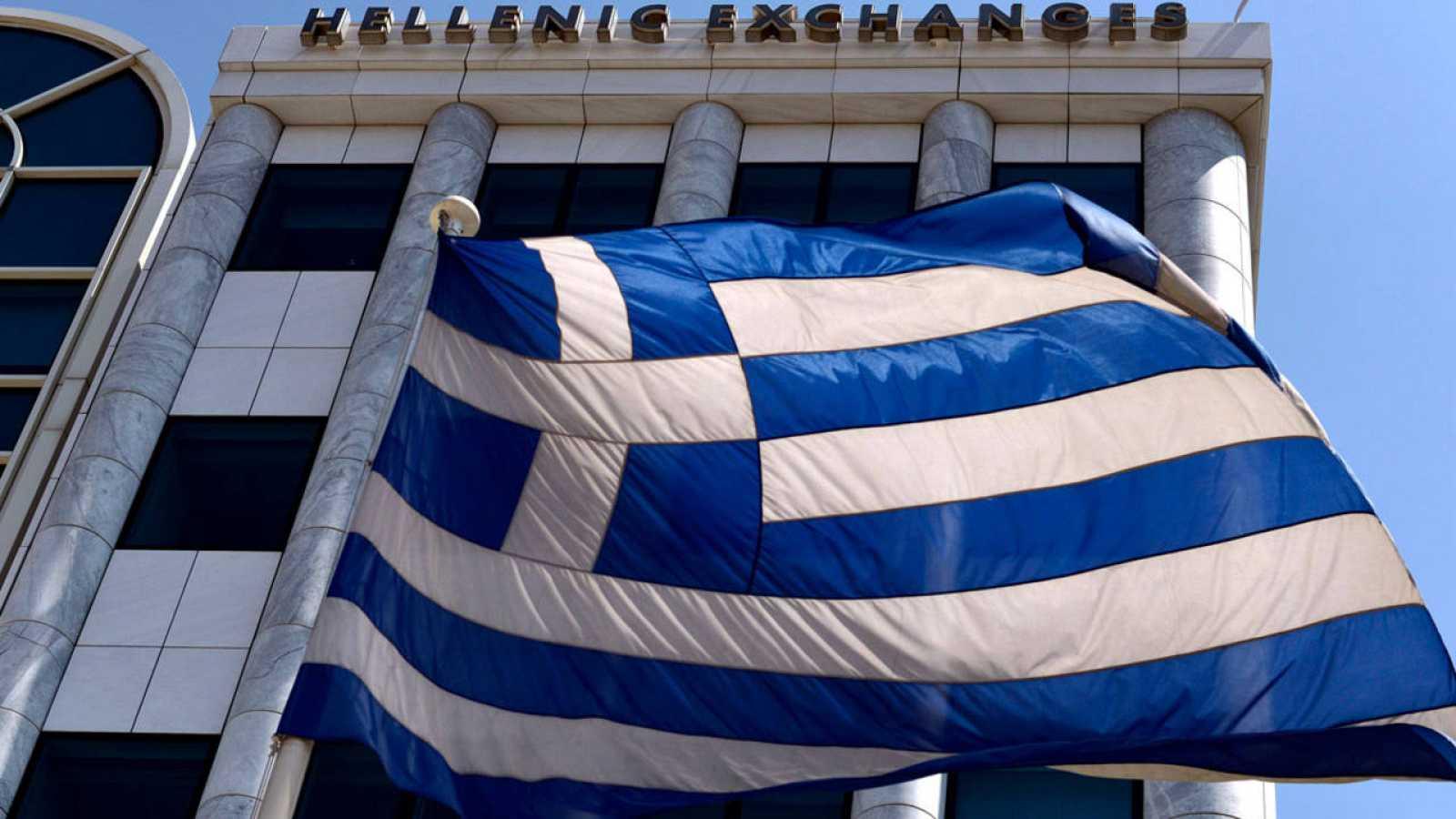 Imagen de una bandera griega que ondea delante de la Bolsa de Atenas