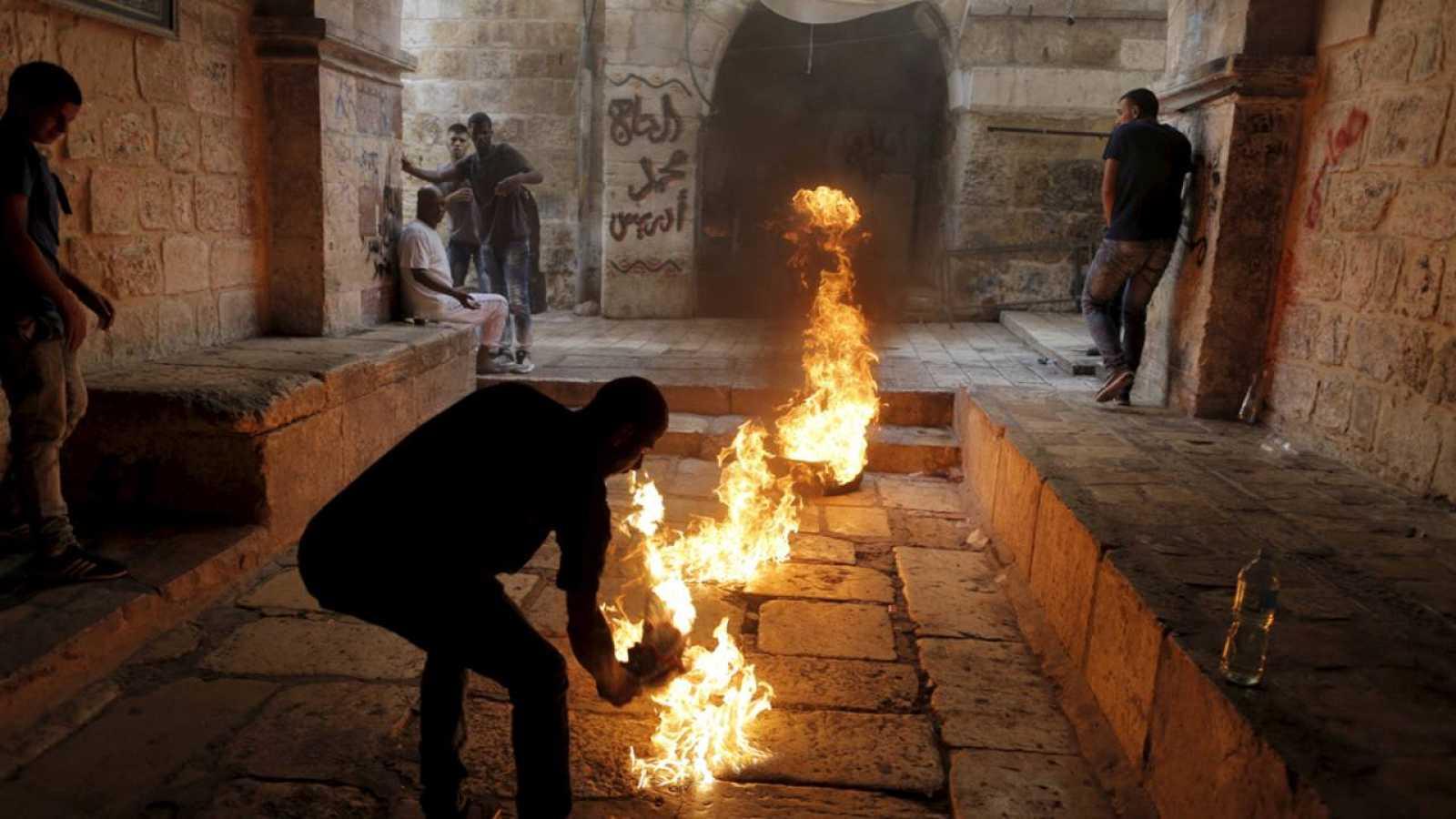 Un manifestante palestino prende fuego a un neumático en el casco antiguo de Jerusalen