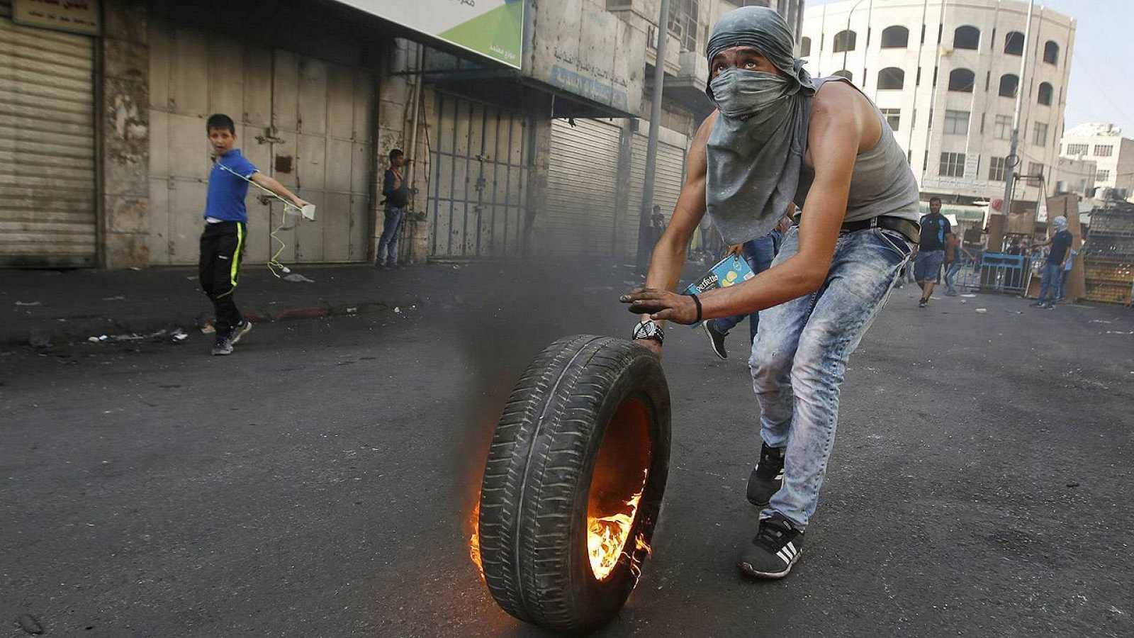 Un palestino empuja un neumático ardiendo durante los enfrentamientos con las fuerzas de seguridad israelíes en Hebrón, sur de Cisjordania, el 4 de octubre de 2015. REUTERS/Mussa Qawasma