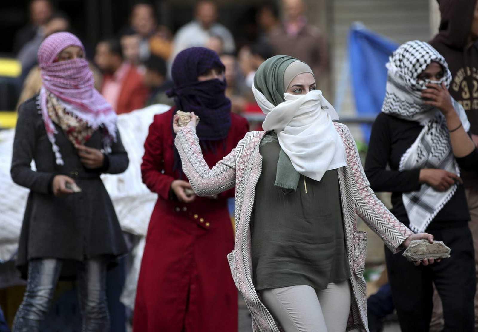 Manifestantes palestinas lanzan piedras durante los enfrentamientos contra las fuerzas israelíes, en Hebrón (Cisjordania), debido a las a escala de violencia en la región.