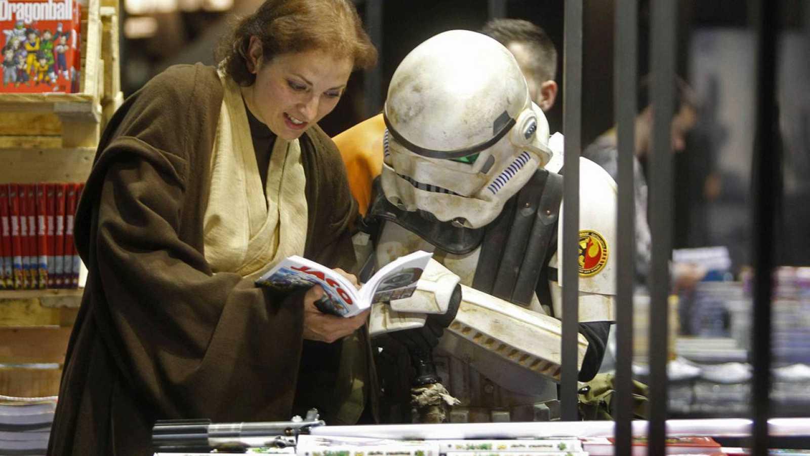 Dos asistentes al pasado Salón del Cómic de Barcelona hojean un libro