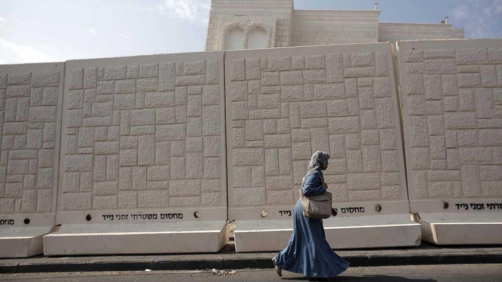 """Una mujer palestina pasa junto a uno de los muros de cemento erigidos por la Policía israelí en el barrio de Yabal Mukaber, en Jerusalén Este. En el muro, en hebreo, se puede leer: """"Barrera policial de separación temporal"""""""