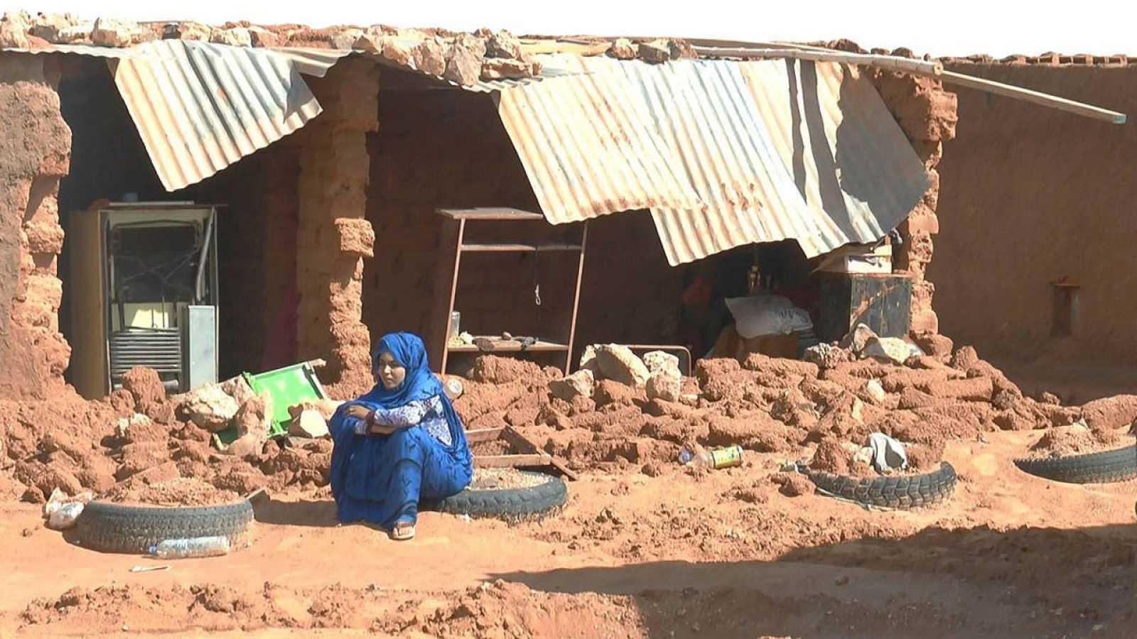 Un mujer sentada junto a los escombros provocados por las lluvias en un campo saharaui