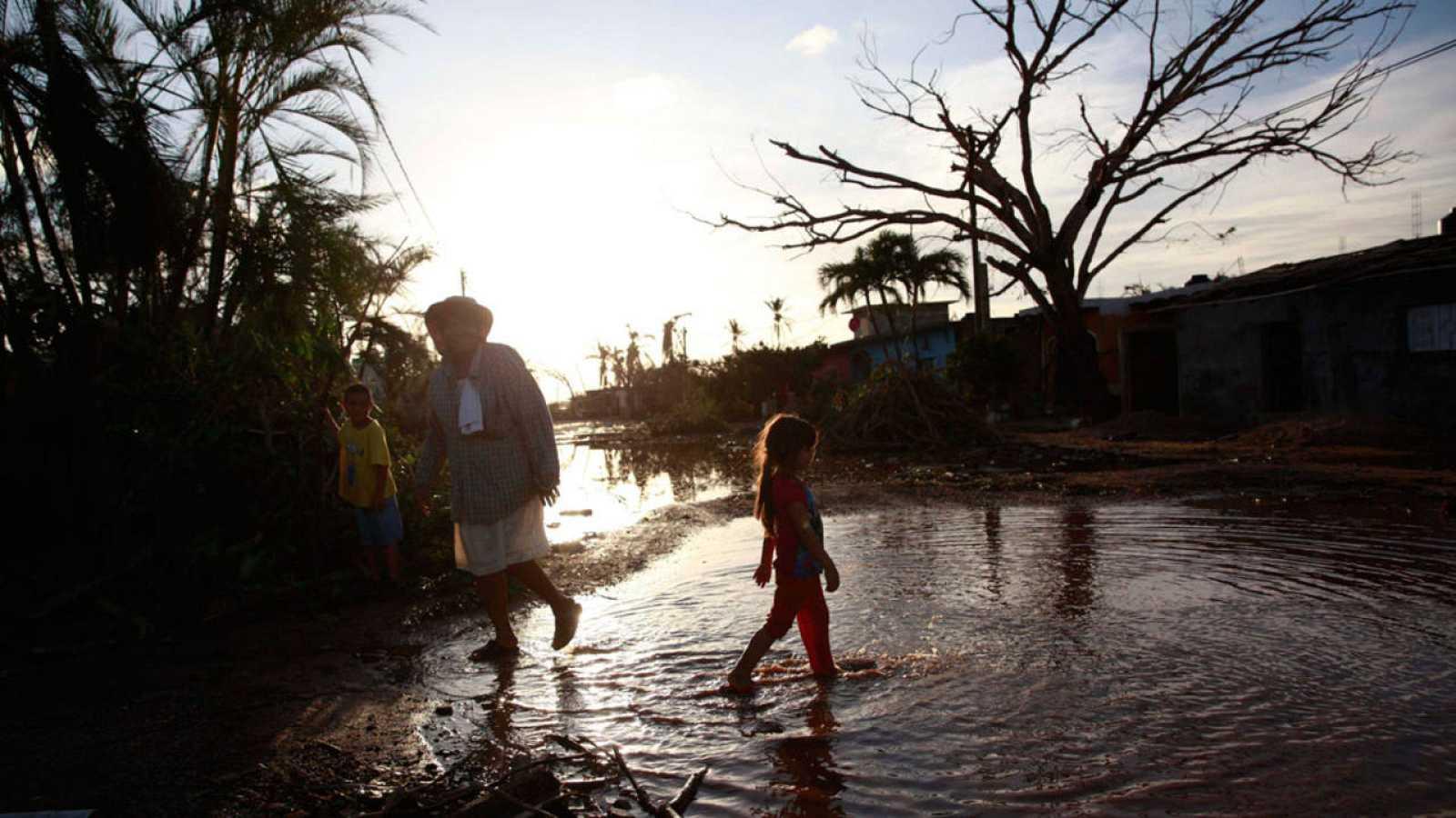 Una familia de la comunidad Emiliano Zapata recorre una calle tras el paso del huracán Patricia en el municipio de la Huerta, en el estado de Jalisco (México).