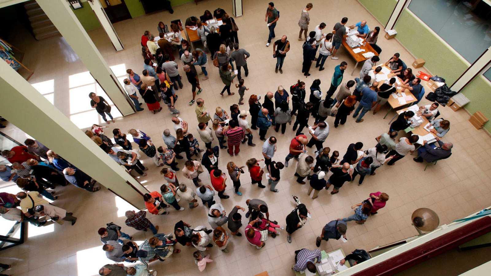Varios ciudadanos hacen cola en un colegio electoral para votar.