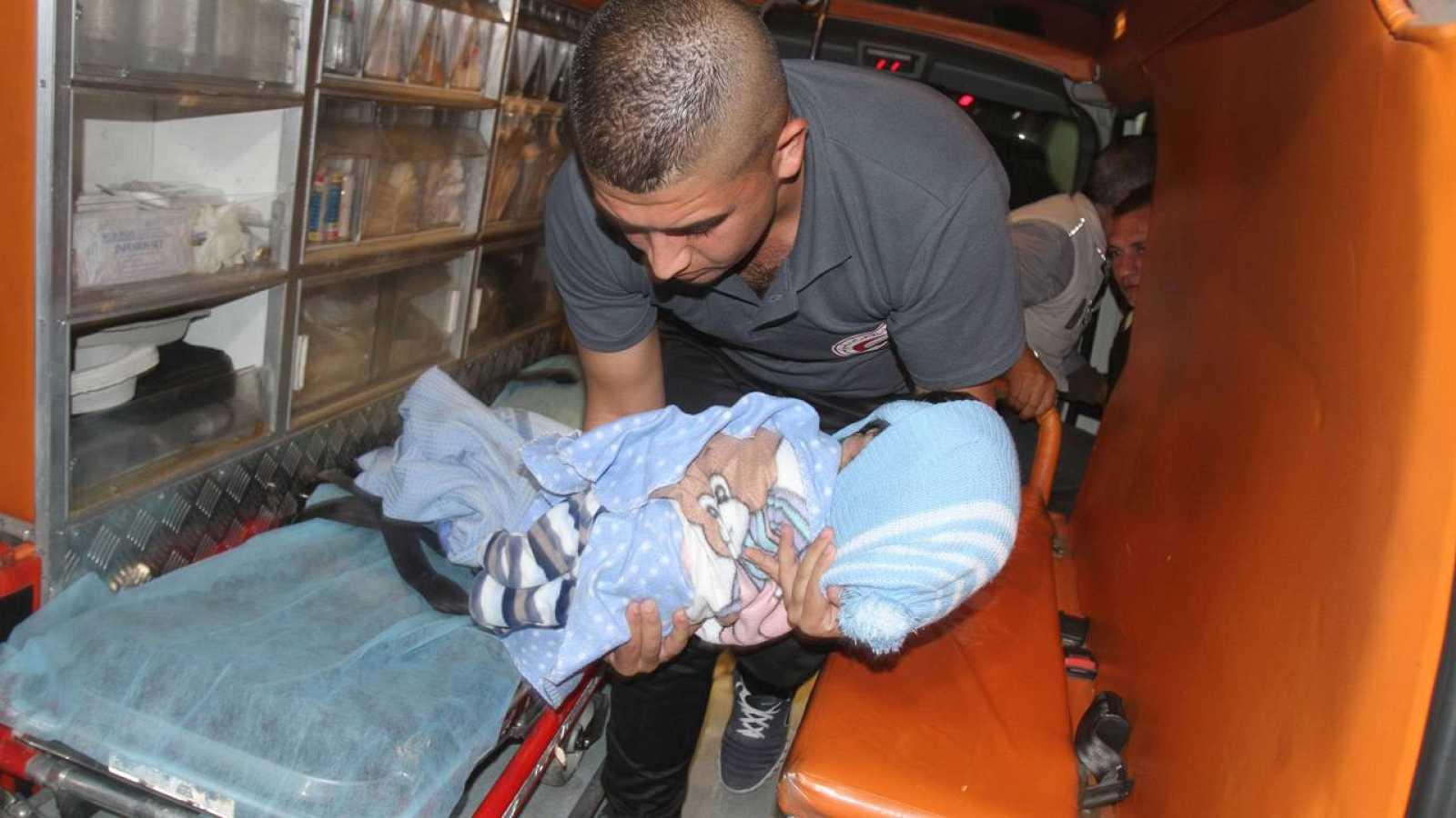 Un sanitario transporta en brazos el cuerpo del bebé palestino Ramadan Thawabteh