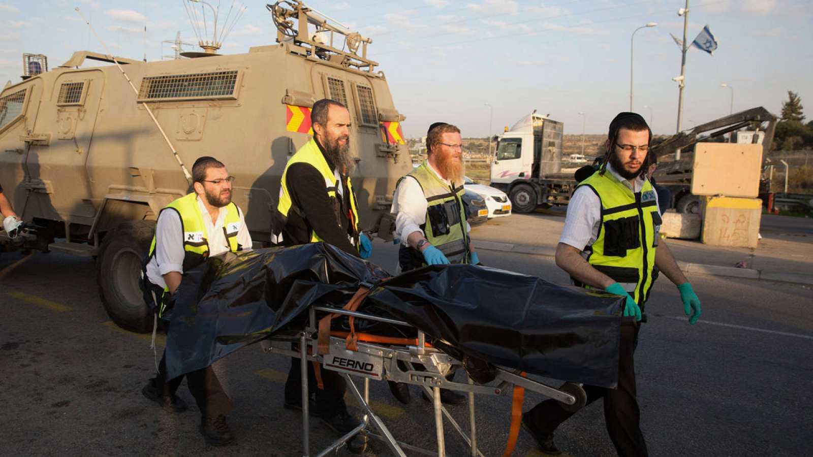 Voluntarios israelíes transportan el cuerpo de un palestino muerto tras apuñalar a una mujer israelí