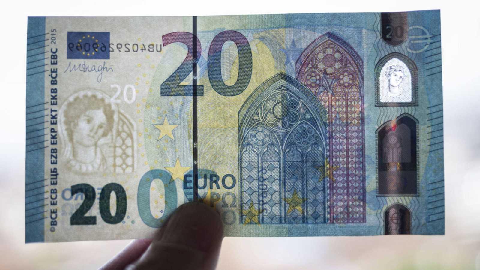 Un miembro del banco federal alemán muestra un nuevo billete de 20 euros durante su presentación en la sede del banco en Fráncfort