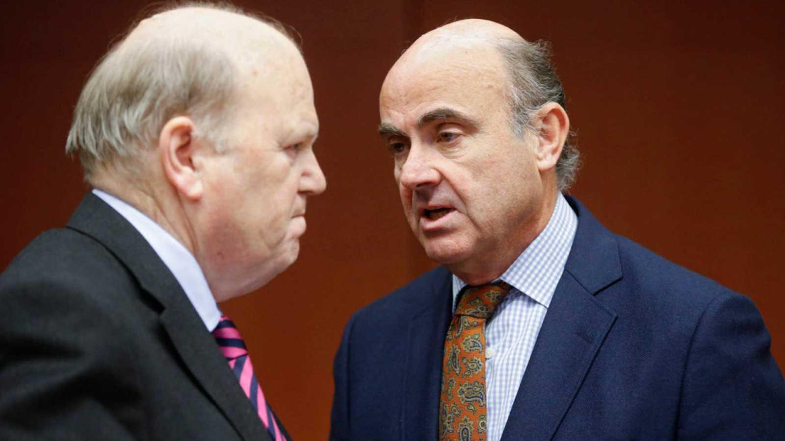 El ministro de Finanzas de Irlanda, Michael Noonan, conversa con el ministro de Economía de España, Luis de Guindos, durante la reunión del Eurogrupo