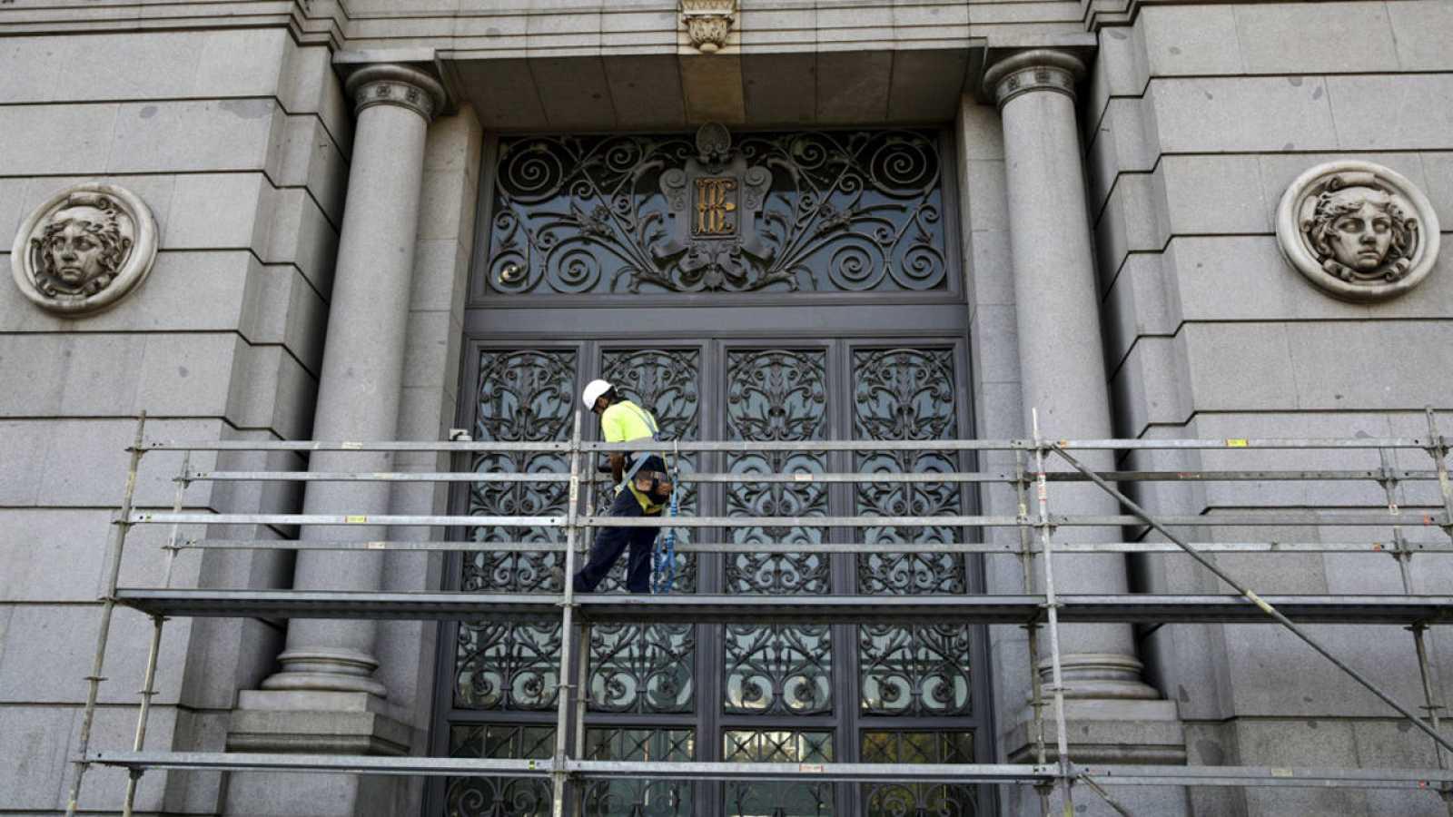 Un trabajador encima de un andamio ante la puerta del Banco de España