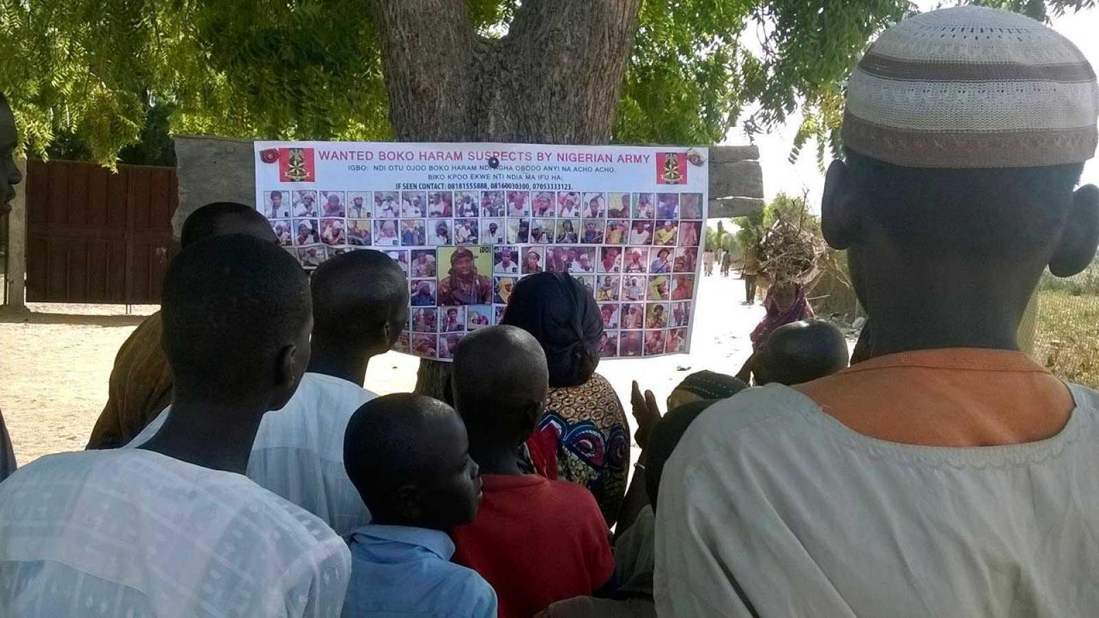 Un grupo de nigerianos observa un cartel con fotos de presuntos terroristas de Boko Haram en busca y captura
