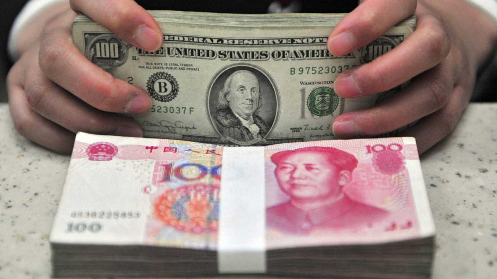 Fotografía de archivo que muestra a una persona contando billetes de yuanes junto con dólares estadounidenses en Shenyang, China