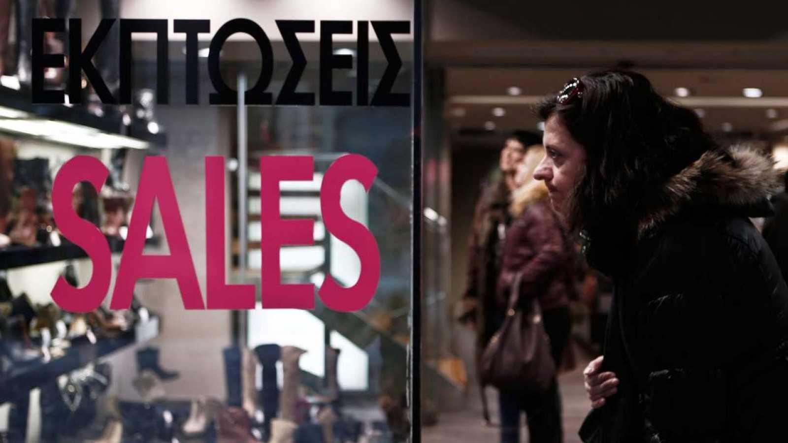 Una mujer mira un escaparate en una calle comercial de Atenas