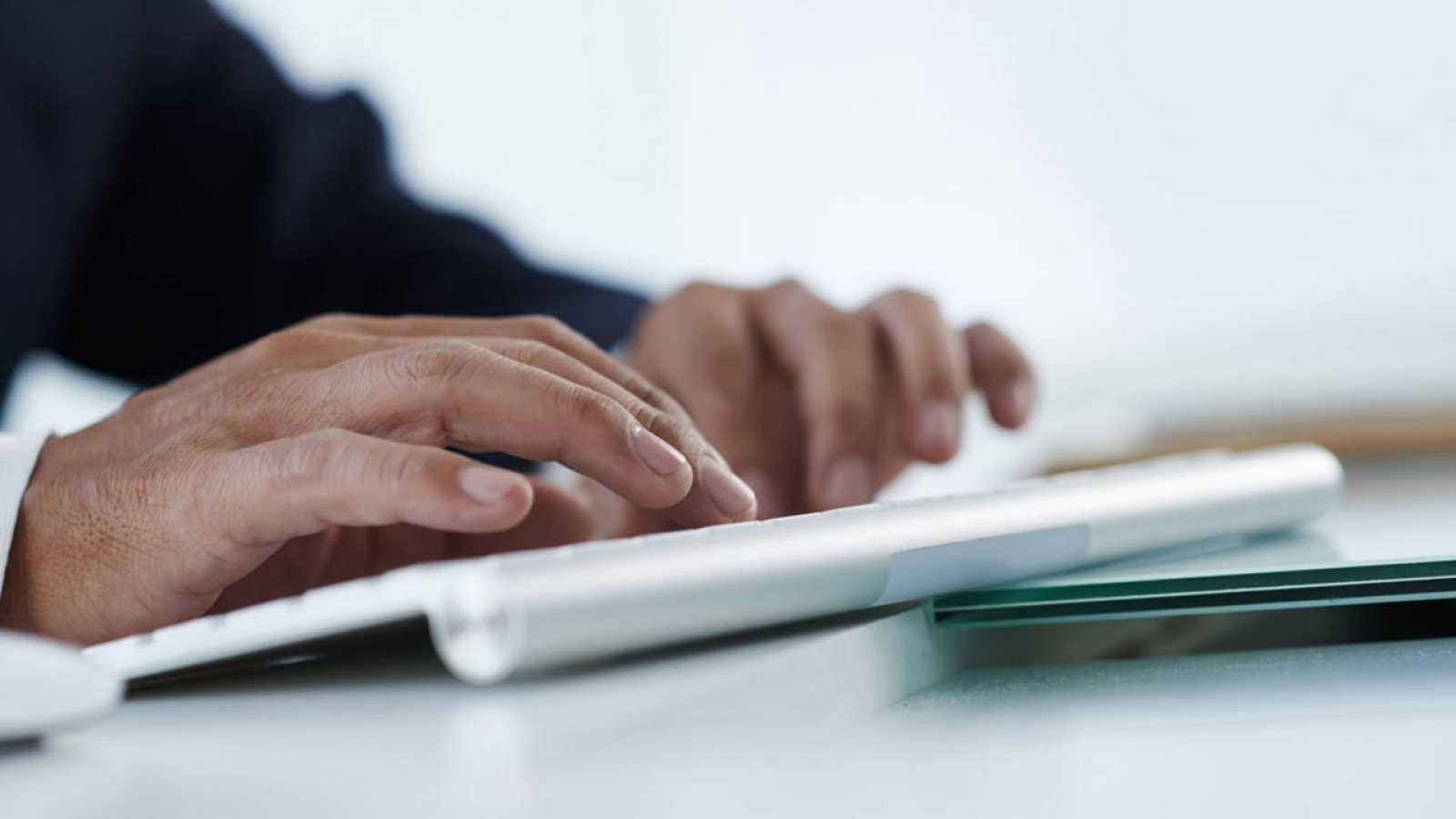 Una persona tecleando en un ordenador
