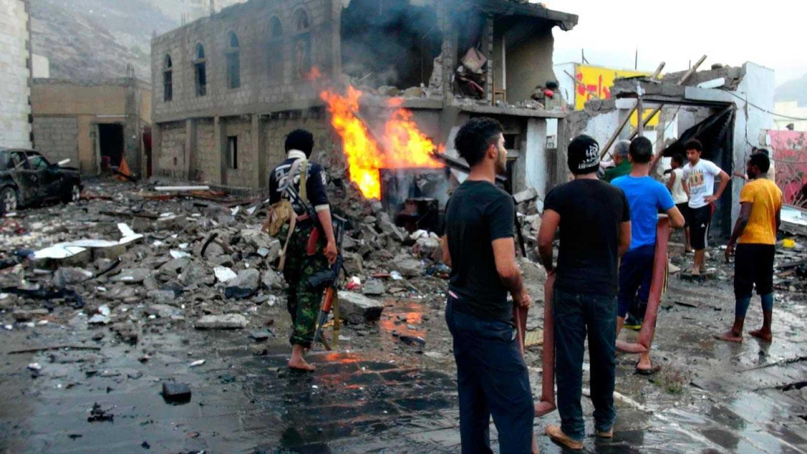 Un grupo de yemeníes observa los destrozos causados por el coche bomba que ha estallado cerca del palacio presidencial de Adén