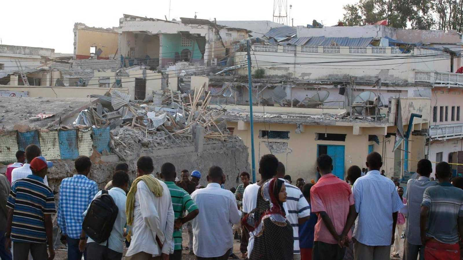 Un grupo de somalíes observan el destrozo causado por un coche bomba de Al Shabab en un hotel de Mogadiscio, a finales de febrero