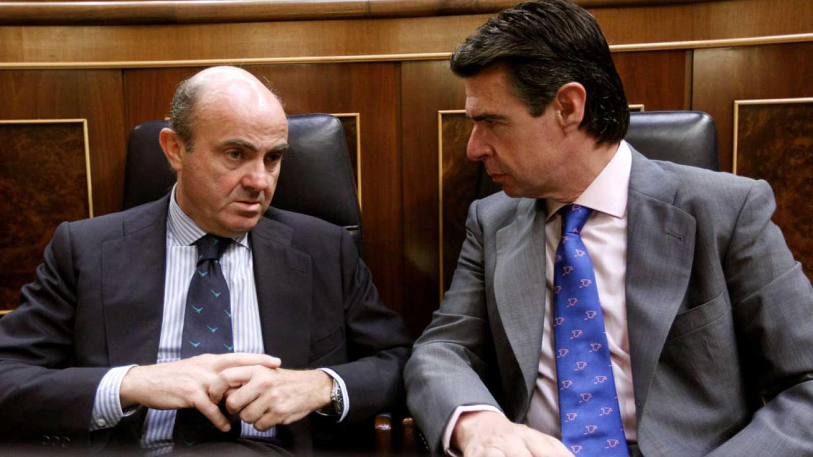 El ministro de Economía, Luis de Guindos, junto al exministro de Industria, José Manuel Soria, en el Congreso