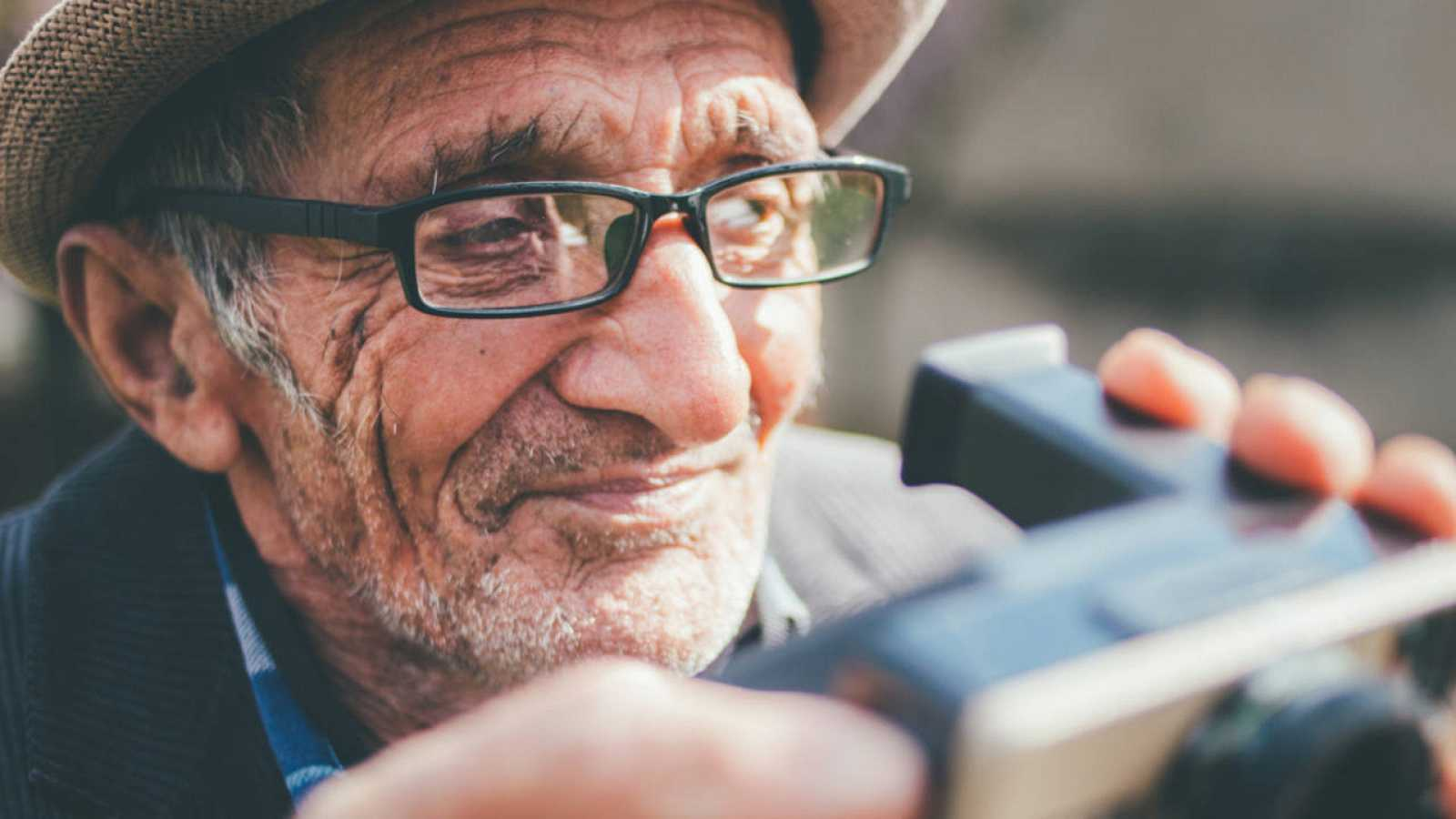 Retrato de un fogógrafo maduro sosteniendo su cámara Polaroid.