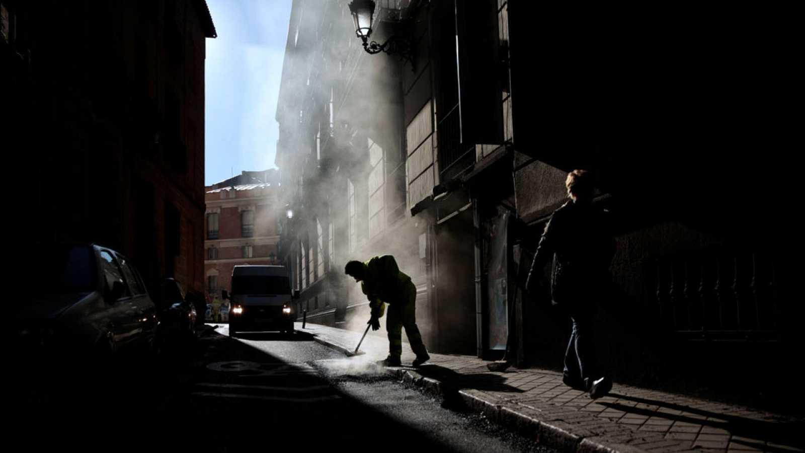 Un empleado limpia una calle de Madrid