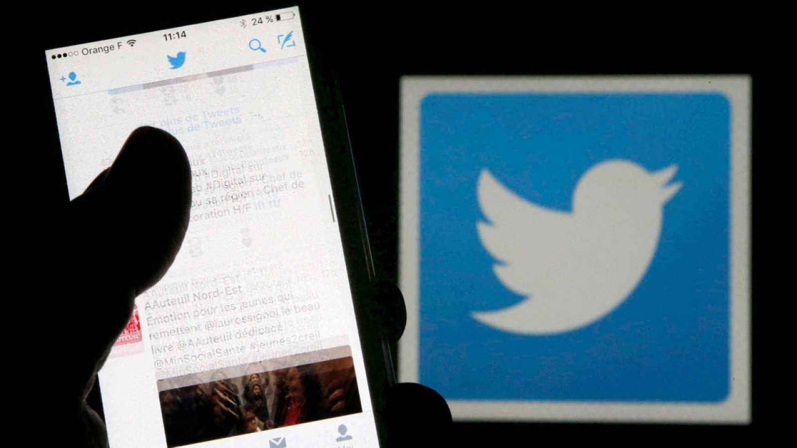 Un hombre utiliza Twitter junto al logo de la compañía en una imagen de archivo.