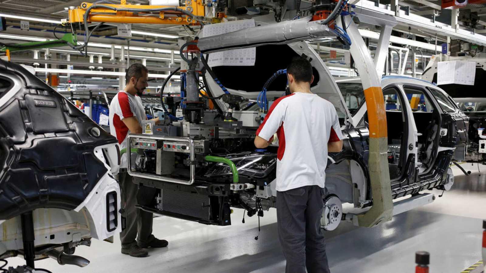 Dos operarios montan el motor de un Seat León en Martorell