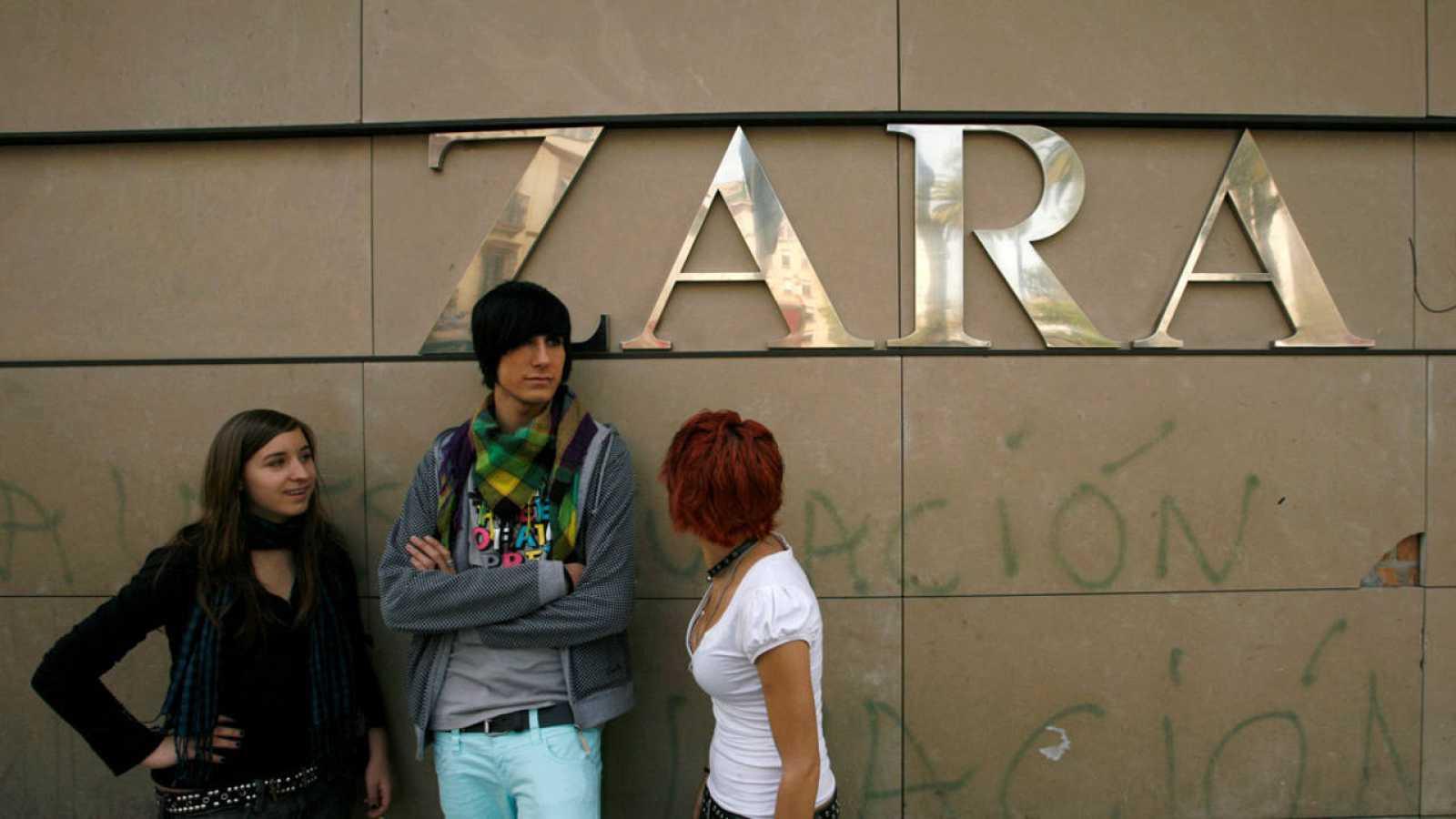 Tres jóvenes charlan en el exterior de una tienda de Zara en Sevilla