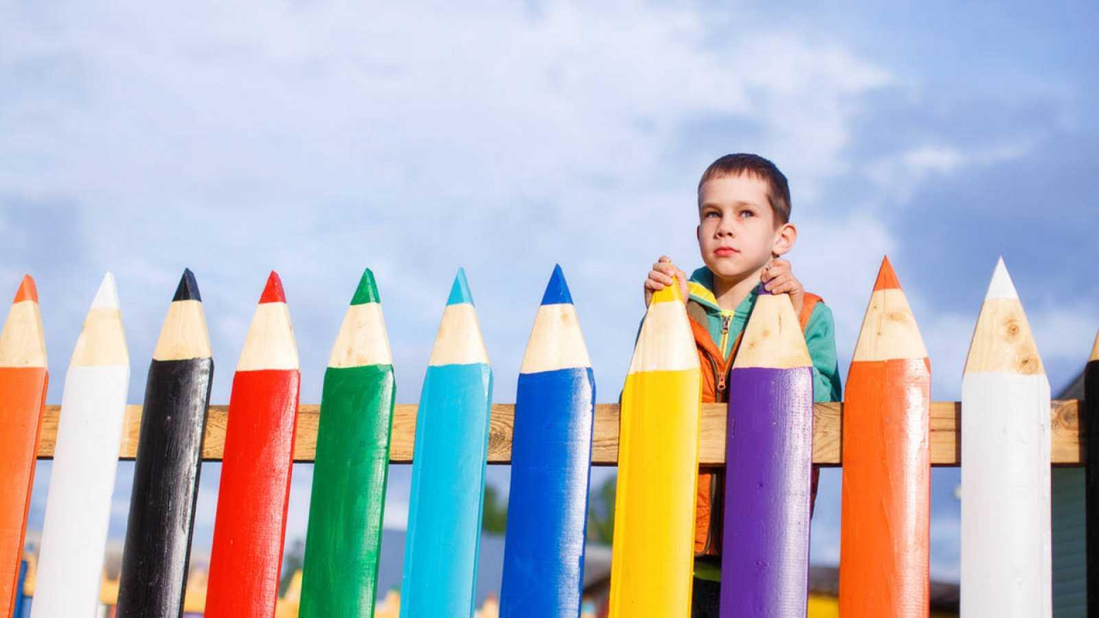 Un niño se asoma a la valla de un parque infantil