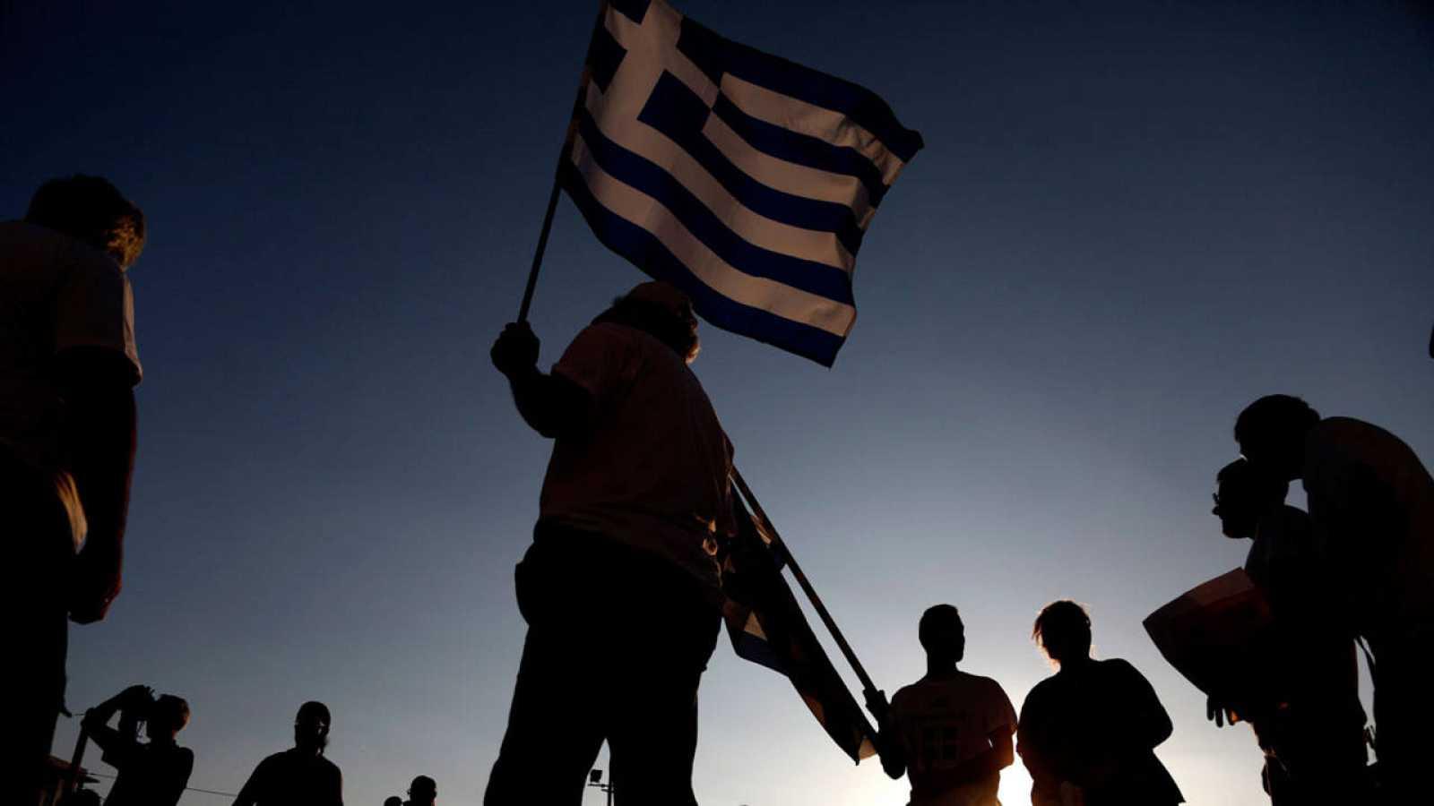 Manifestantes antigubernamentales enarbolan una bandera de Grecia