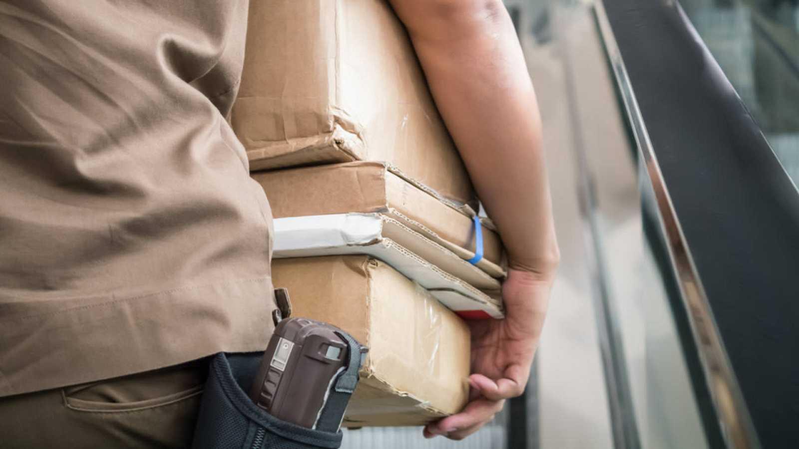 Un trabajador de una empresa de mensajería carga varios paquetes
