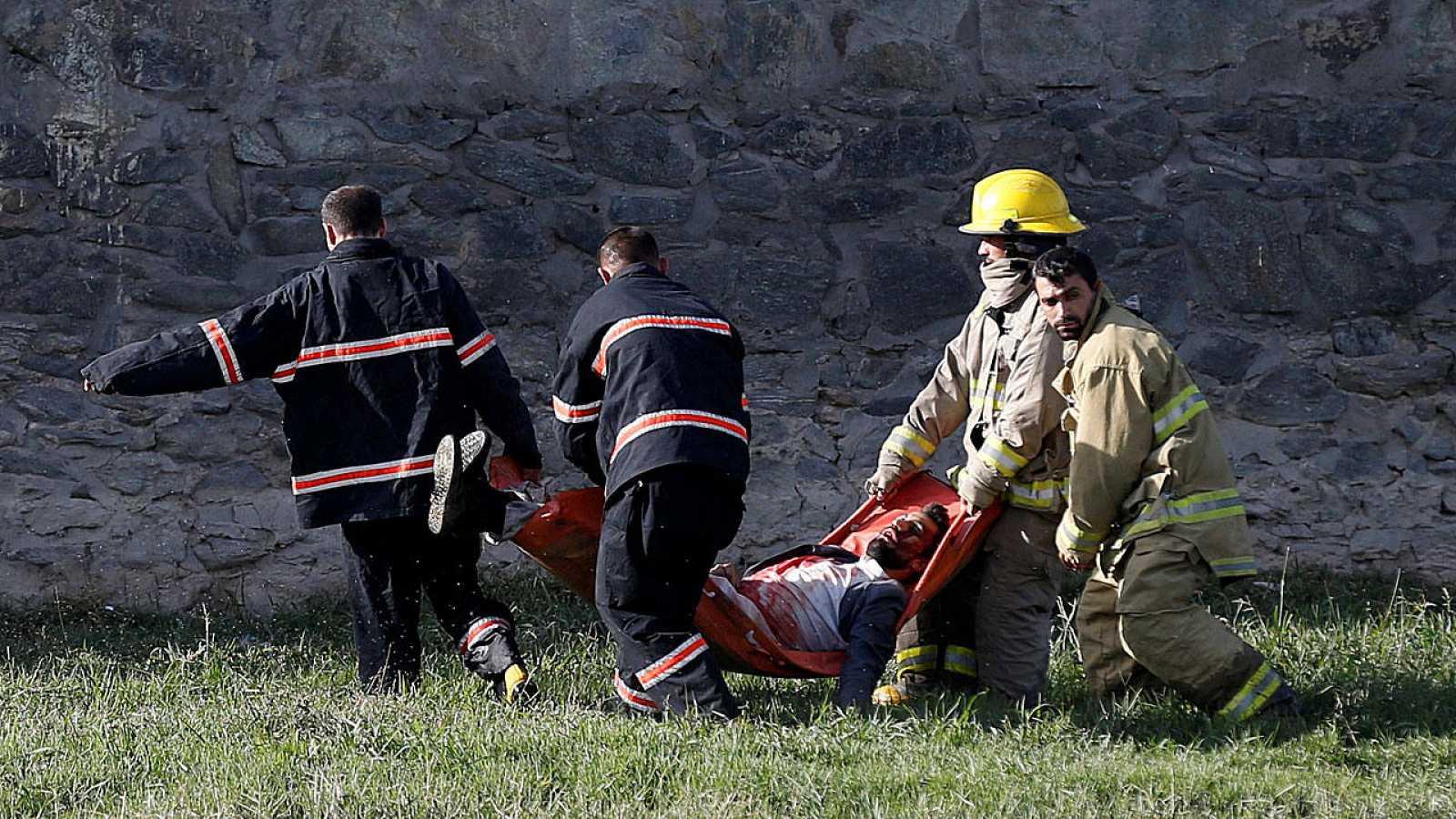 Los equipos sanitarios y de seguridad trasladan a una de las víctimas del atentado contra el Ministerio de Defensa en Kabul.
