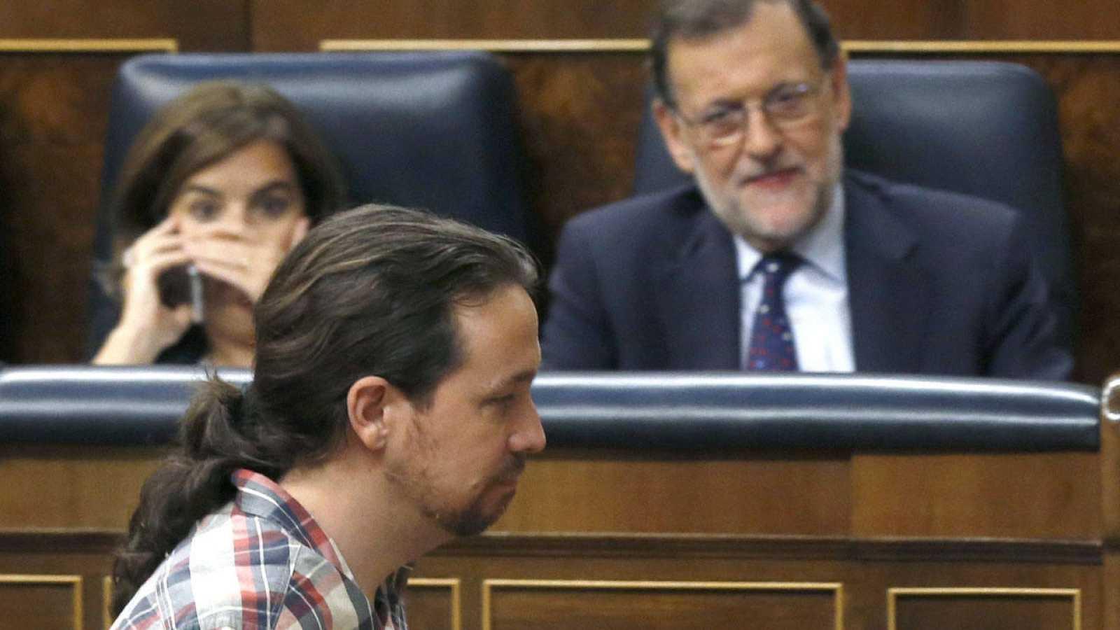 El líder de Podemos, Pablo Iglesias, pasa por delante del presidente en funciones, Mariano Rajoy