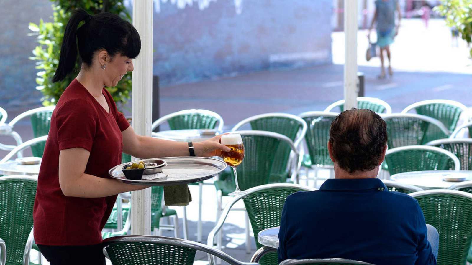 Una camarera sirve una consumición en una terraza de Valladolid