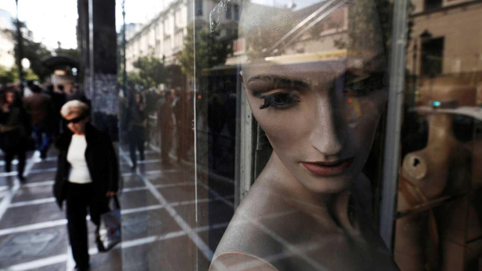 Una mujer camina junto a una tienda cerrada en Atenas, Grecia