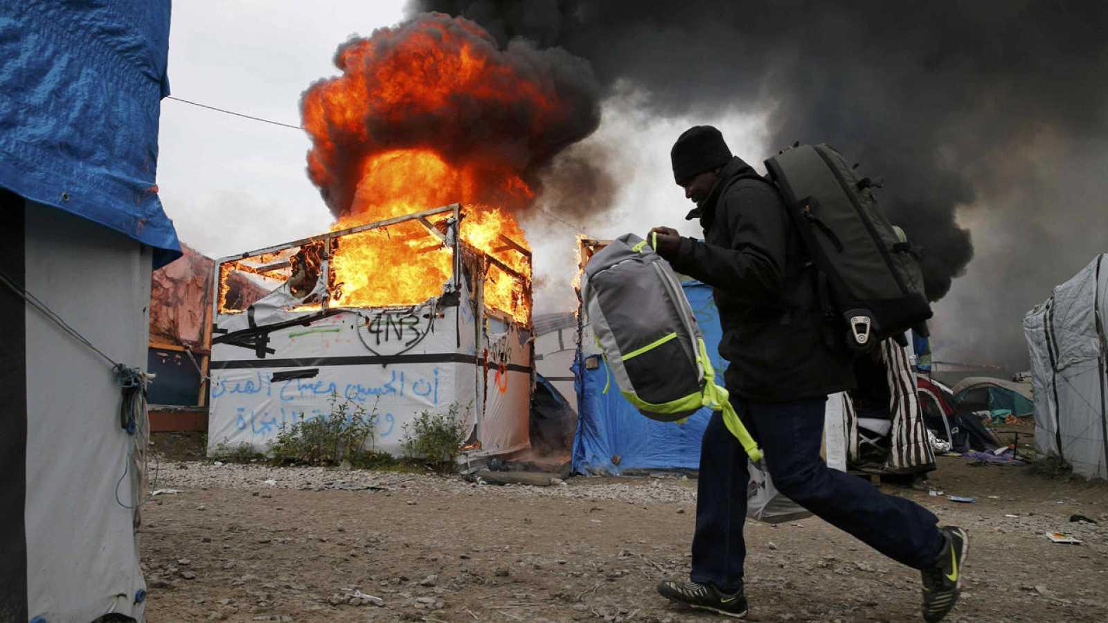 Un migrante pasa con sus pertenencias junto a una chabola en llams en 'La Jungla' de Calais