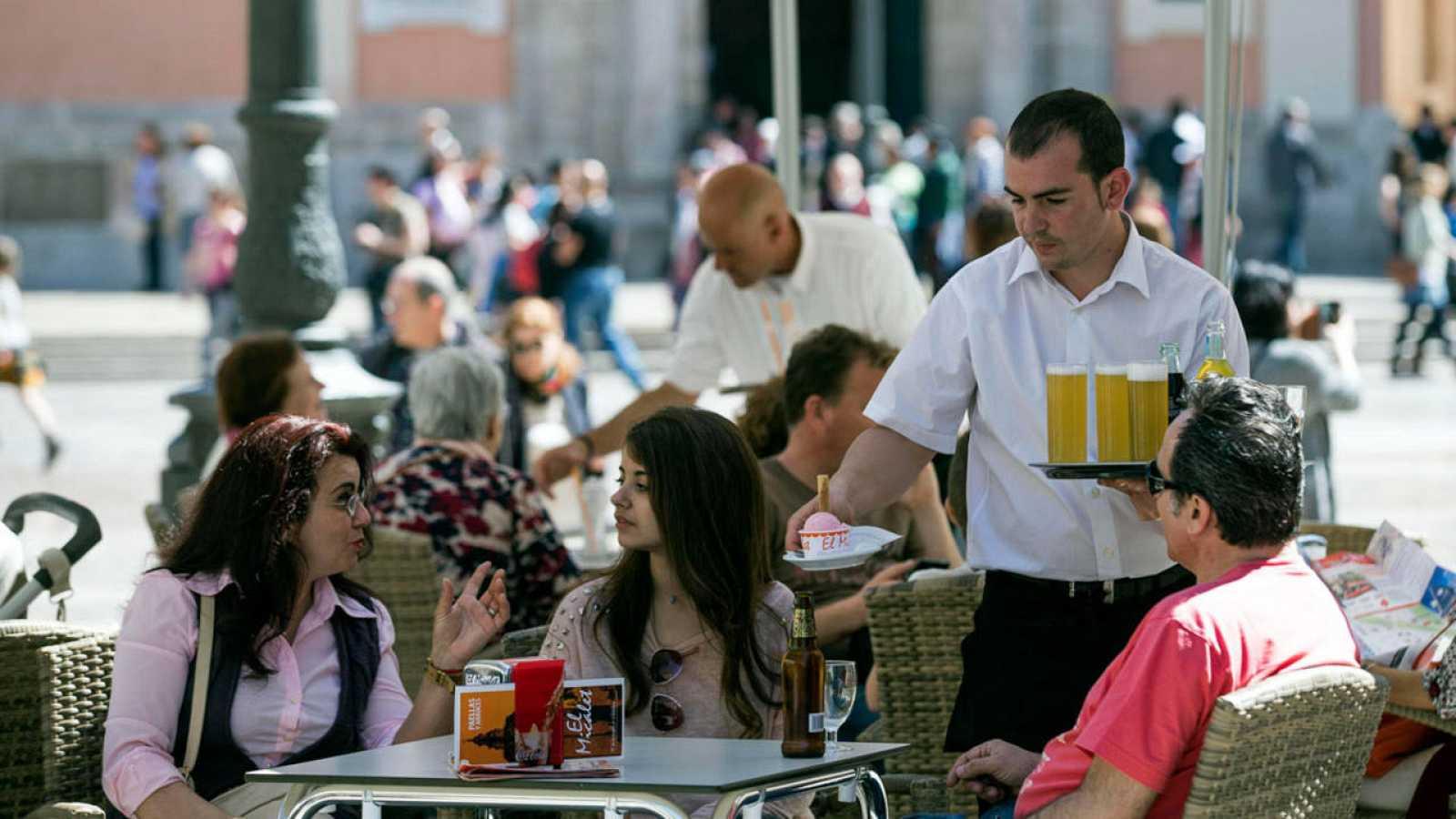 Imagen de archivo de un camarero sirve bebidas en una terraza en Valencia