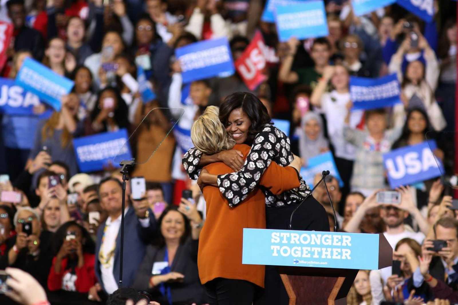 La candidata demócrata Hillary Clinton y la primera dama Michelle Obama se abrazan en su primer mítin juntas, en Carolina del Norte.