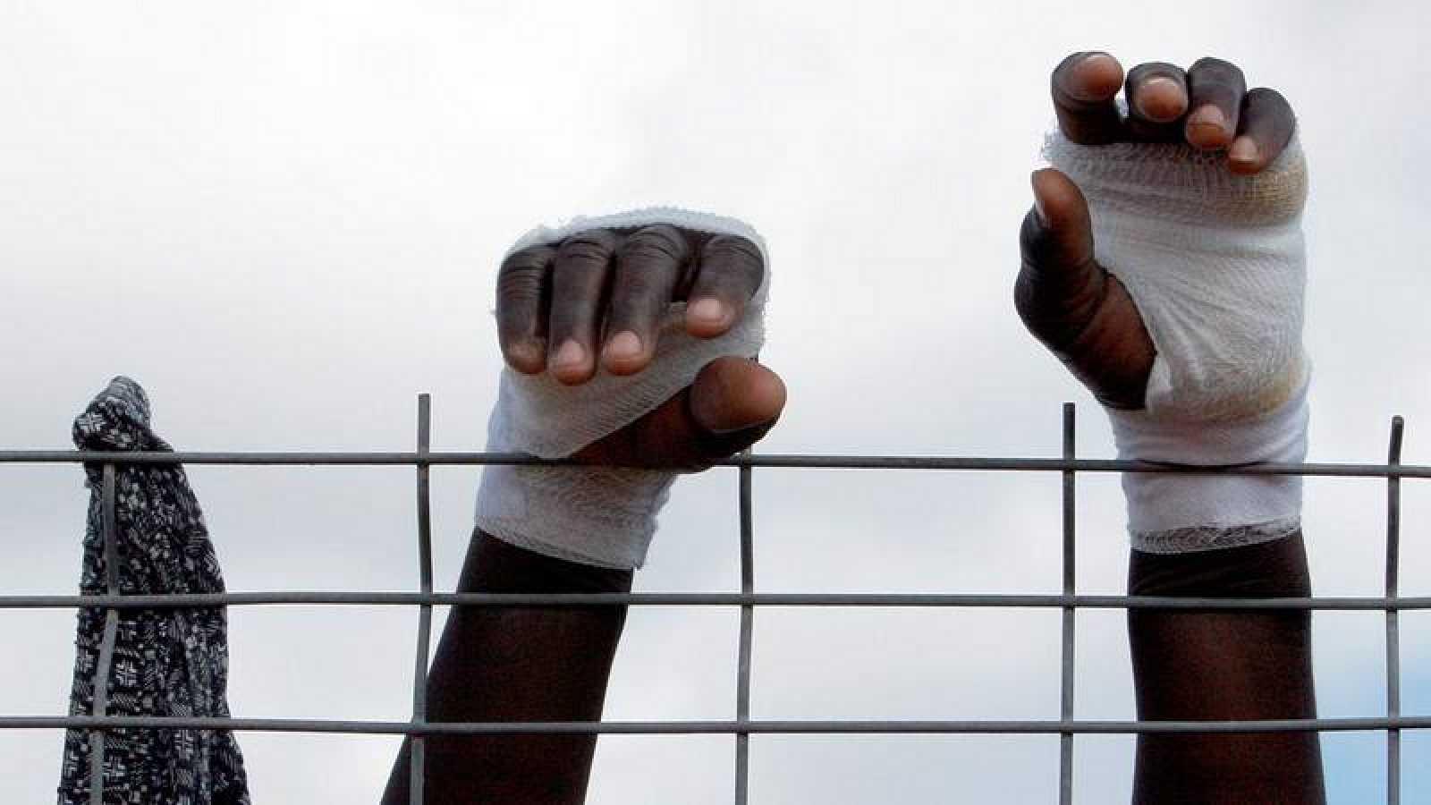 Un imigrante trata de superar la valla de entrada a Melilla con las manos protegidas para evitar cortes