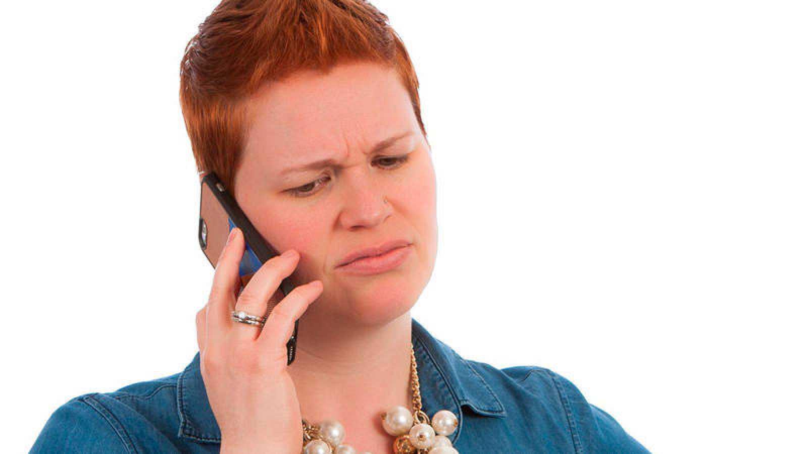 Una joven habla por su teléfono móvil con gesto de disgusto