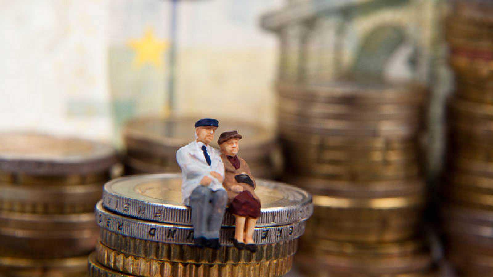 Imagen alegórica de las pensiones:dos ancianos sentados sobre una pila de monedas
