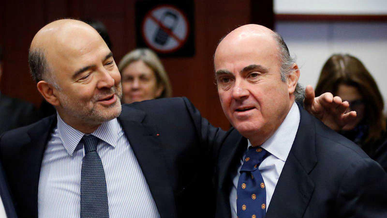 El comisario europeo de Asuntos Económicos y Financieros, Pierre Moscovici (i), y el ministro de Economía español, Luis de Guindos