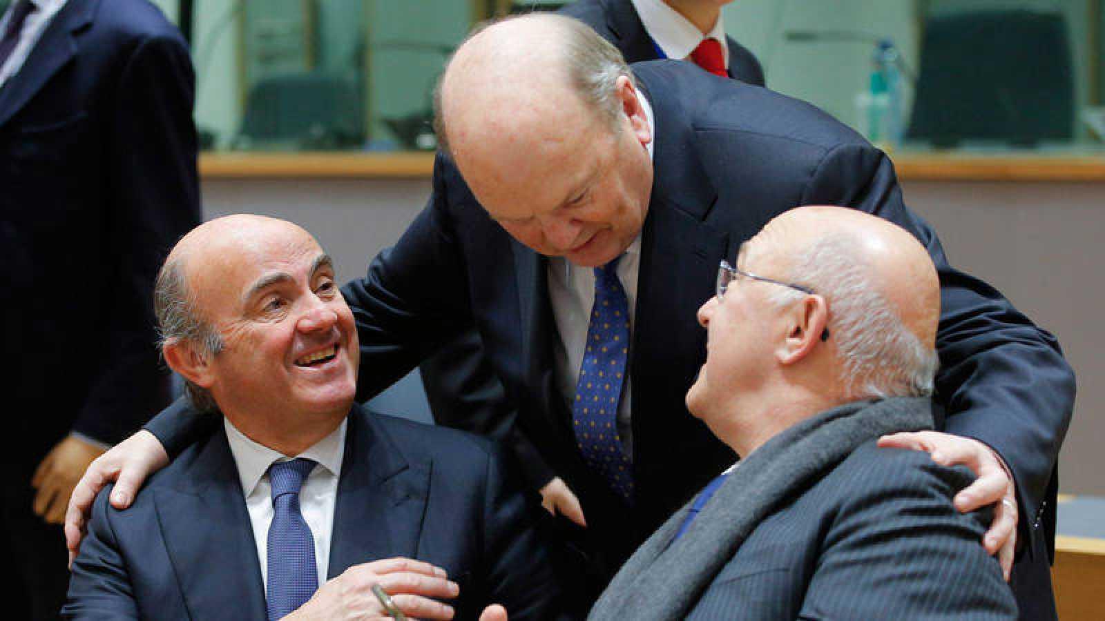 El ministro de Economía español, Luis de Guindos, conversa con el ministro de Finanzas francés, Michel Sapin ,y su homólogo irlandés, Michael Noonan, durante la reunión de ministros de Economía y Finanzas de la eurozona (Eurogrupo) en Bruselas