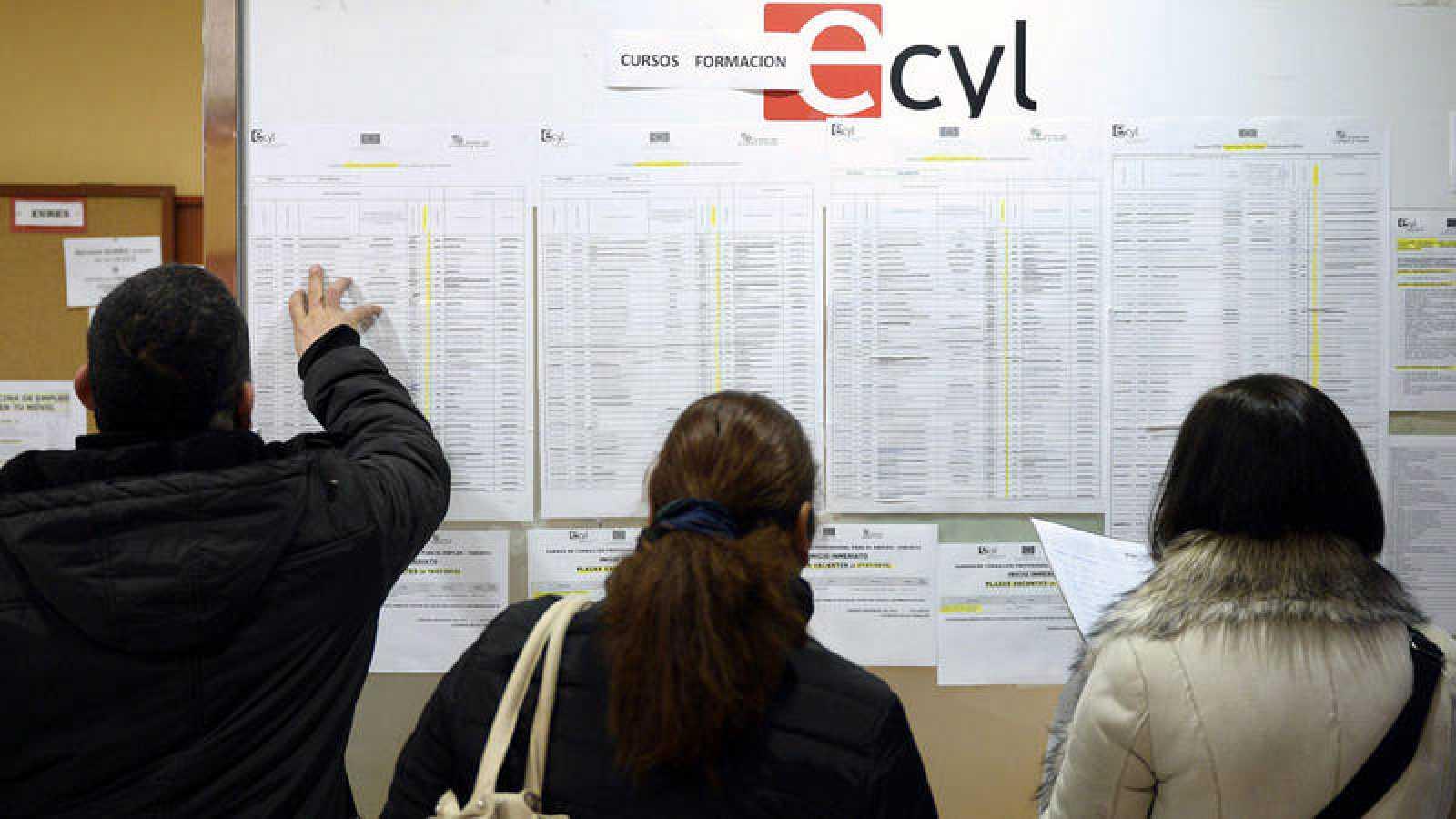 Tres personas consultan la información expuesta en una oficina de empleo de Valladolid.