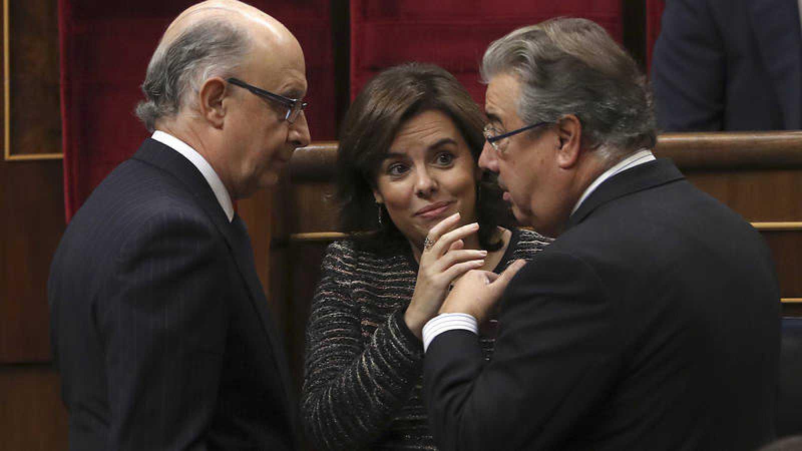 La vicepresidenta del Gobierno, Soraya Sáenz de Santamaría, junto con el ministro de Hacienda, Cristóbal Montoro y el de Interior, Juan Ignacio Zoido