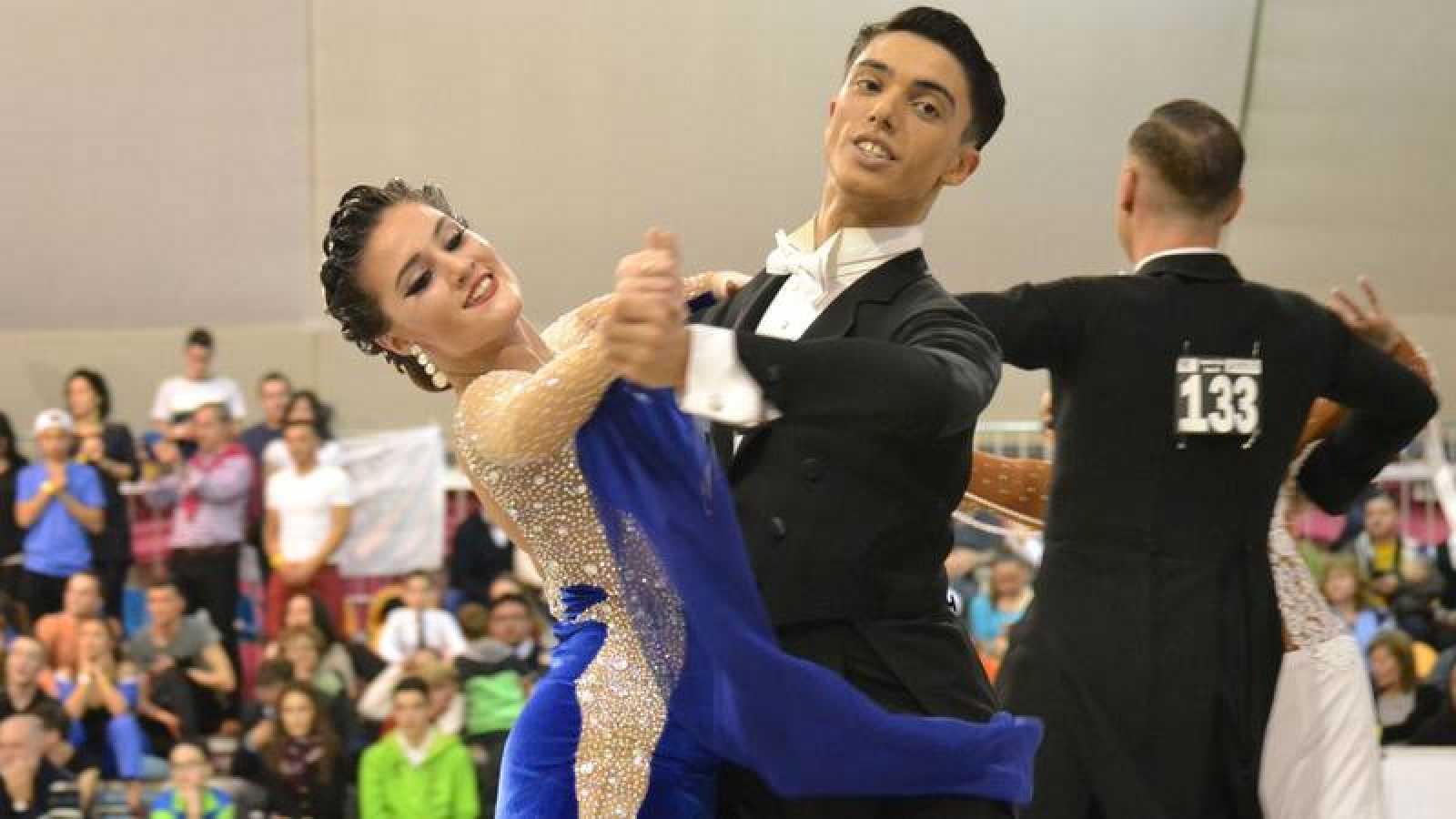 Una pareja baila en un campeonato de baile deportivo standard