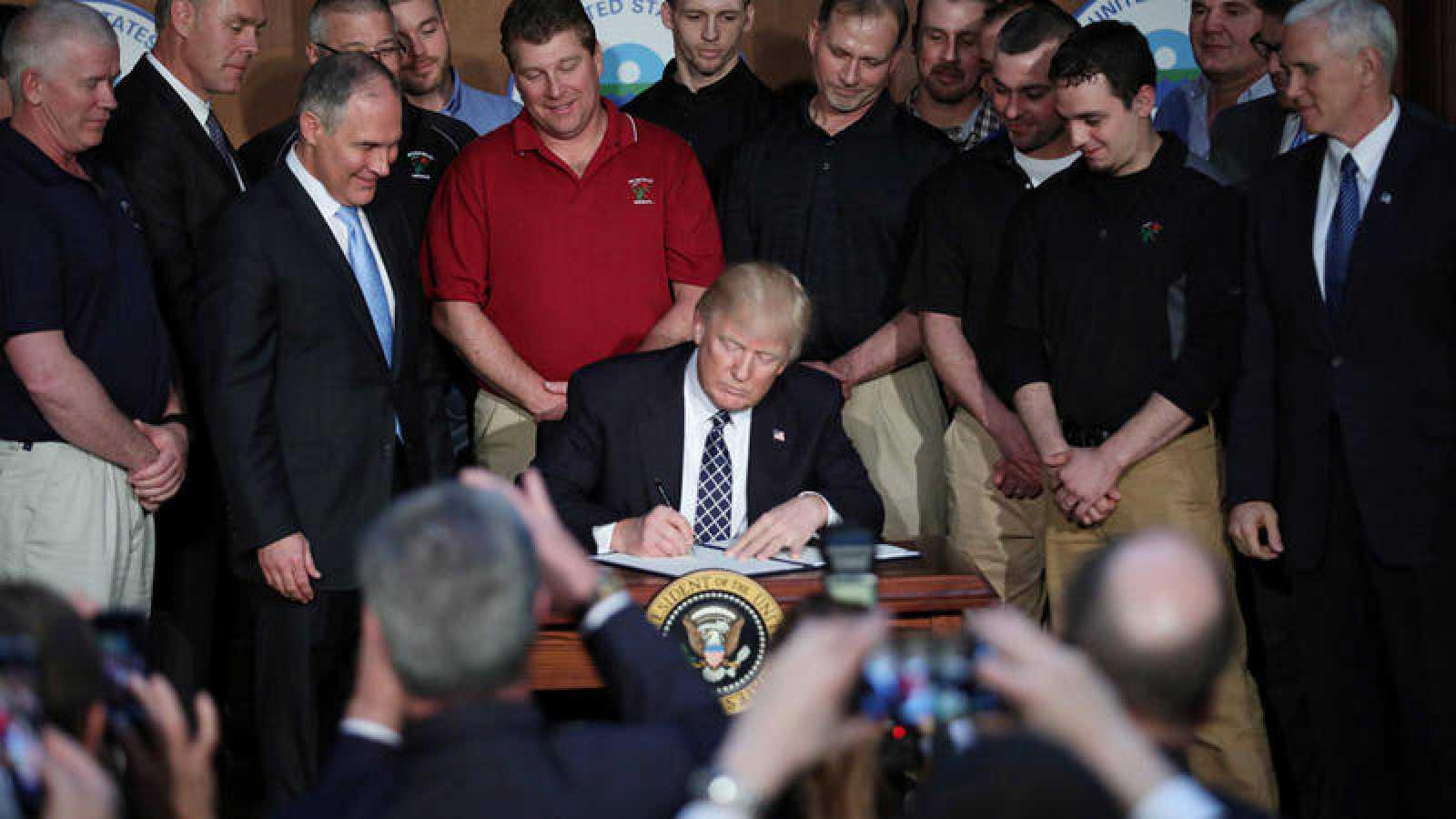 """Momento en que el presidente de EE.UU., Donald Trump, firma el decreto de reforma del plan contra el cambio climático de Obama y a favor de la """"independencia energética"""" del país."""