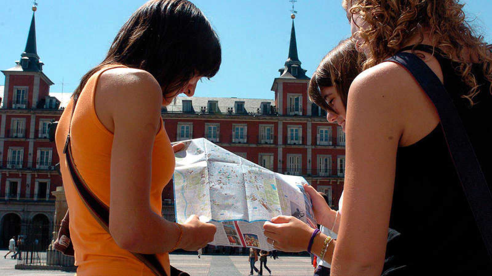 Imagen de archivo de tres turistas con un plano en la Plaza Mayor de Madrid